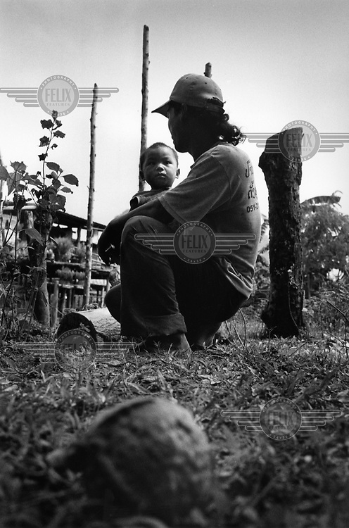 Mr Toeng whith his son Tang sit close to a cluster bomb submunition unearthed in their garden. More than two million tonnes of ordnance was dropped over Laos ruring the Second Indo-China War, an estimated 30 per cent of which did not explode on impact. UXO still affects more than 25 per cent of Lao villages