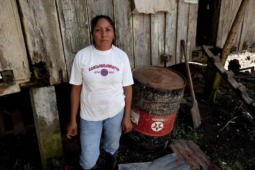 Maria Hortencia Punina, 38, on a farm owned by her father Carlos Punina in 12 de Noviembre of San Carlos.  She has lived on the farm for 32 years after Texaco left and did not know the area was polluted with petroleum. They once grew animals, but a cow, 2 pigs, and other animals fell in the pit and died almost immediately.  She later lost two sisters while living on the farm;  22-year-old sister died three years ago of toxication. She says the ¨Consejo Provincial¨ has done tests and demonstrated that the area is polluted.