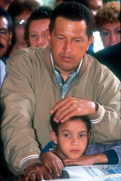 Venezuelan President Hugo Chavez during a visit to the Caracas neighborhood of Catuche in January 2000 following Dec 1999 flooding. Here he looks over plans for rebuilding of the community while touching head of boy who wandered into meeting.