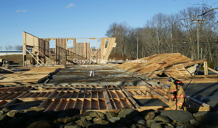 OXFORD, CT, 01/09/08- 010908BZ03- Oxford firefighters walk past the remains of a building under construction on Riggs Street in Oxford that partially collapsed in high winds Wednesday afternoon.<br /> Jamison C. Bazinet Republican-American