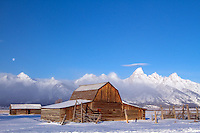 Full moon over the John Moulton Barn beneath the Grand Tetons on a crisp winter morning<br />