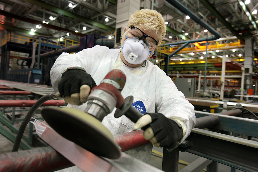 "Theresa Haller sands a long, thin aluminum ""stringer""-one of many that will be used to help form the inner structural grid of a new airplane's wing, to which its outer skin is attached. Boeing employees who do this type of work wear full protective gear that includes gloves and safety glasses, as well as breathing masks and Tyvek coats which protect them from dust."