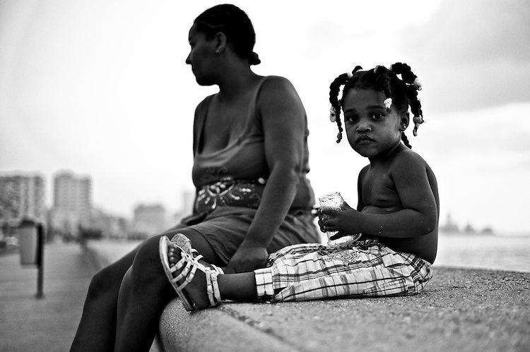 Images from the old Havana, Cuba. ..Girl in the malecon at sunset.