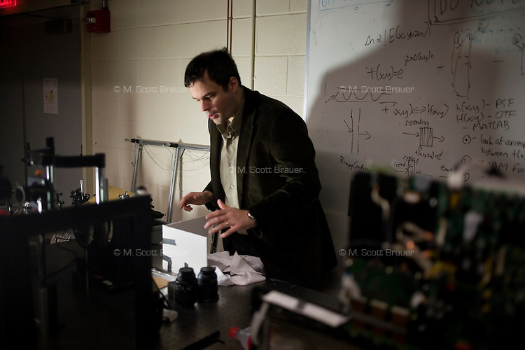 Dr. Andreas Velten, Postdoctoral Associate in Dr. Ramesh Raskar's Media Lab Camera Culture group, sets up equipment in a lab at MIT in Cambridge, Massachusetts, USA.  Velten and Raskar's group has developed a camera that records at 1 trillion frames per second, which allows, for example, the recording of pulses of light moving through a liquid.