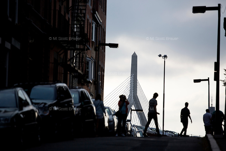 People walk near Copp's Hill Burying Ground on Hull Street in the North End of Boston, Massachusetts, USA. In the background, one can see a view of the Leonard P. Zakim Bunker Hill Memorial Bridge.  The cemetery is the second oldest in Boston and has the remains of many people from the colonial Boston era.