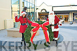 CHRISTMAS DE?COR: Carly Horan Marketing Executive of Central Plaza Retail Centre helping Santa put up the Christmas Decorations at the Plaza on Friday.