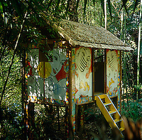 A thatchted hut on stilts painted with female faces stands amidst the bamboo in the garden