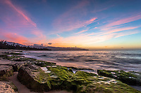 Colorful sunset with algae covered rocks on the shore of Papailoa Beach, North Shore, Oahu, Hawaii