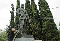 Pictured: A protester is using an angle grinder to try and cut the statue of Harry S. Truman in Vassileos Georgiou Street in central Athens, Greece. Monday 16 April 2018<br /> Re: Clashes broke out between protesters and the police when members of the Greek Communist Party (KKE) attempted to vandalise the statue of former US President Harry S. Truman, during a protest against the bombing of Syria by the US and its allies.