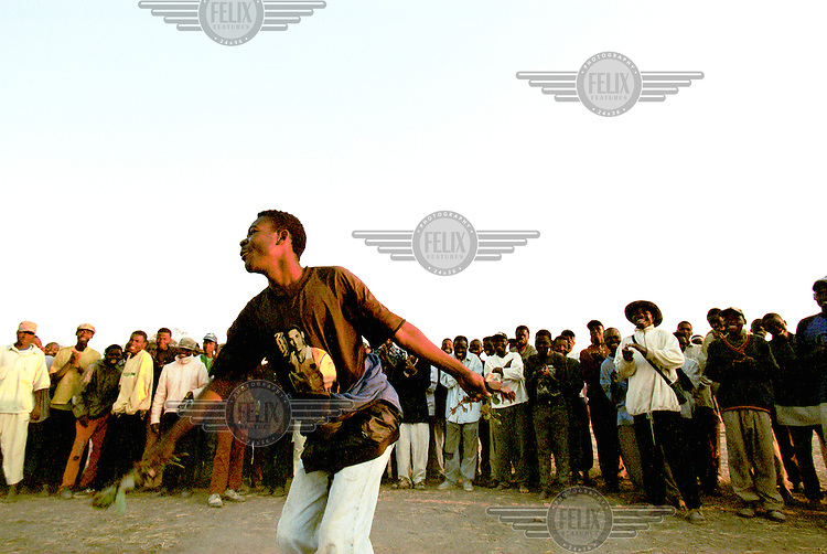 © J.B. Russell / Panos Pictures..Sambo, Angola. 06/08/2002...UNITA soldiers dance and sing at a dawn assembly in quartering area for more than 4000 demobilized UNITA soldiers and their families in a remote village. The area will see a huge influx of people displaced by the war as they return to their former village, however there is no food, no seeds for planting and the area is heavily mined.
