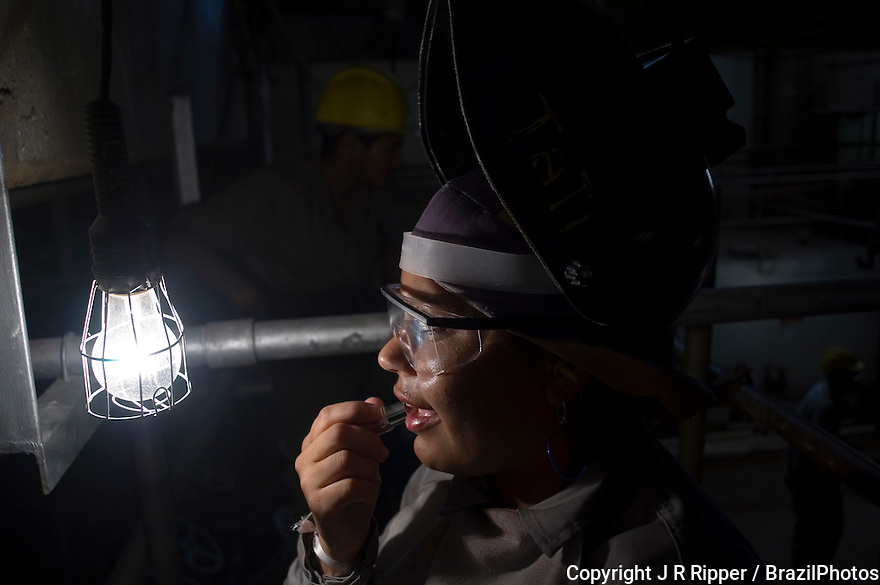 Workwoman ( welder ) applies lipstick during coffee break in a power substation, energy distribution system, Brazil.