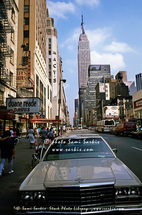 Car parked in a downtown street with the Empire State Building in the background, Manhattan, New York, USA.
