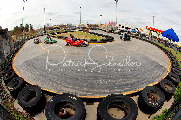 Photography of Concord Mills Mall, a 1.4 million-square-foot mall located in Concord, NC, about 12 miles from Charlotte, NC. In this image, visitors experience action on the track at NASCAR Speed Park located at the mall. Photo is part of a photographic series of images featuring Concord, NC, by photographer Patrick Schneider.