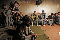 """Members of the Afghan Uniformed Police (AUP) meet with their American counterparts that live in the next-door base - the AUP are housed in what was once a school that was almost destroyed when the Taliban attempted to overrun the adjacent American base in 2011. The commander of the AUP, Arman Shaah is in the foreground. Combat Operating Post Zerok - manned by members of Attack Company, 1-28 IN, 4IBCT/1ID is located in Eastern Paktika - this area comprises what is referred to as the """"Zadran Arc"""", an area populated by the Zadran tribe of Jalaluddin Haqqani, the leader of the Haqqani network, one of Afghanistan's deadliest insurgent movements. COP Zerok, Paktika, Afghanistan 2012. (PHOTO: Javier Manzano)."""