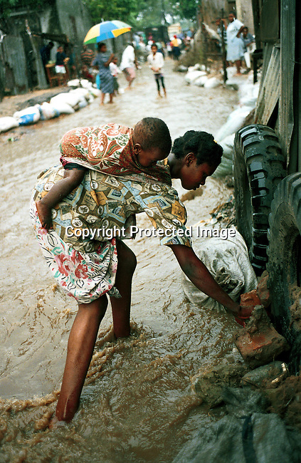A mother and child in central Maputo, Mozambique. The woman is trying to repair the family house as the rain is pouring down during the flooding that hit Mozambique in February-March 2000. .©Per-Anders Pettersson/iAfrika Photos