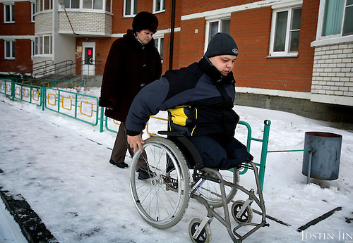 Russian army hazing victim Andrei Sychyov uses a wheelchair outside his home in Yekaterinburg, closely followed by his mother, Galina Sychyova. .On New Yearís Day in 2006 in the barracks of the Chelyabinsk Tank Academy, a sergeant, possibly drunk, meted out punishment to Pvt. Andrei S. Sychyov..Private Sychyov was forced to squat for three and a half hours. When he complained, as the pain worsened, the sergeant stomped on his ankle twice..Private Sychyov suffered injuries that resulted in infection, then in the amputation of his both legs, a finger, and genitals. .His case became the biggest scandal to reflect the state of Russia's army and the country's human rights situation.