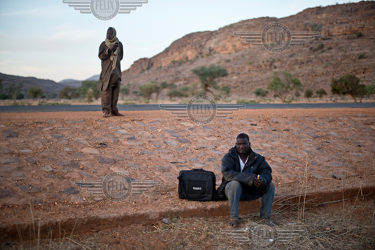 A passenger waits on the roadside, near Douentza for transport to Timbuktu.