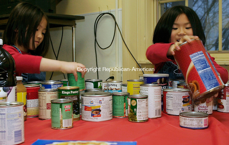 MIDDLEBURY, CT- 23 MARCH 2005-032305J02--Susanne Kulpa, 6, of Middlebury, left and her sister LeighAnn, 7, sort donated food items during the Middlebury Town Committee's annual family pasta night. The food will benefit the Middlebury Food Bank.   --- Jim Shannon Photo-- Susanne Kulpa, LeighAnn Kulpa; Middlebury; Middlebury Town Committee; Middlebury Food Bank are CQ
