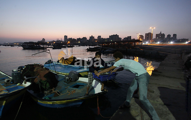 Palestinian fishermen work on their boat during the sunrise at the Gaza seaport in the west of Gaza City, 02 September 2013. The Egyptian navy boats attacked the Palestinian boats off the southern Gaza Strip last Friday, near the border with Egypt, wounding fishermen and the arrest of 5 fishermen. Photo by Ashraf Amra