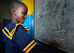 A child writes on a blackboard during class in a day care center in Monrovia, Liberia, sponsored by United Methodist Women.