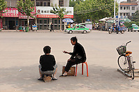 Daytime landscape view of two women sitting and talking on a sidewalk next to a road in Bozhou in Qiáochéng Qū in Anhui Province.  © LAN