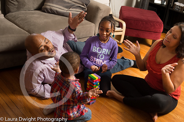 Family at home playing game with colored blocks all reacting to gesture from two year old boy that the structure is finished, mother and father imitating his gesture, 7 year old sister looking on