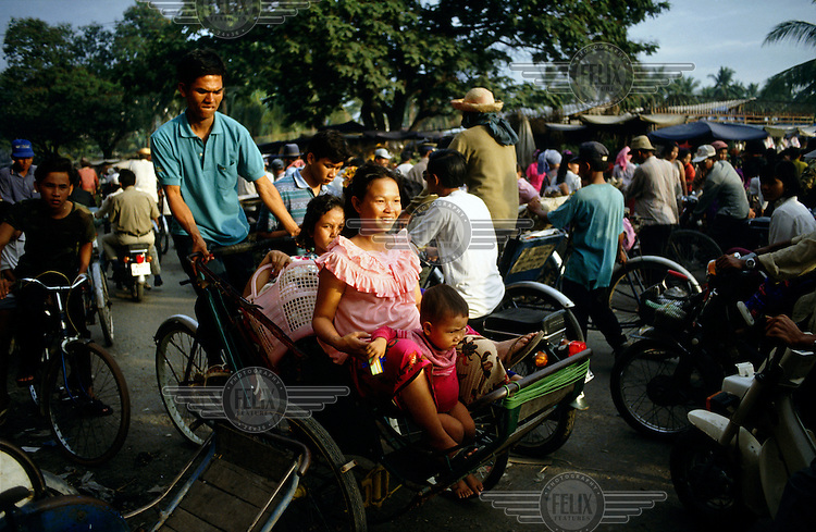 A cycle carrier about to unload a family at the entry to a city market during rush hour.