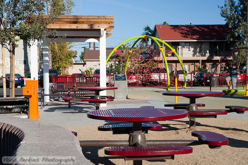 The picnic area at Circle Park, a small pocket park in Anaheim, CA.  Visible are tables, a barbecue, water fountain, pergola, and play structures.  A child is using one of the play structures in the background.