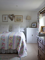 A feminine touch to this bedroom is introduced by a pretty quilted bedcover and floral curtains