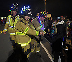 Members of the Ellington Volunteer Fire Department adorned with Christmas lights on their helmets, hand out candy to children during a torchlight parade, part of the Ellington annual winterfest and tree-lighting ceremony, Saturday, December 2, 2017, on Main Street in Ellington. Shown here are Ellington firefighters, from left,  Randy Smith, Nicole Hazzard and Brad Hoffman.(Jim Michaud / Journal Inquirer)