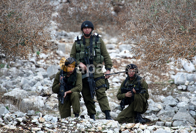 Israeli border police officers fire tear gas toward Palestinian demonstrators, who are seeking access to their land near Kufr Qaddum, near the northern West Bank Jewish settlement of Kdumim, Friday, Nov. 18, 2011. Photo by Wagdi Eshtayah