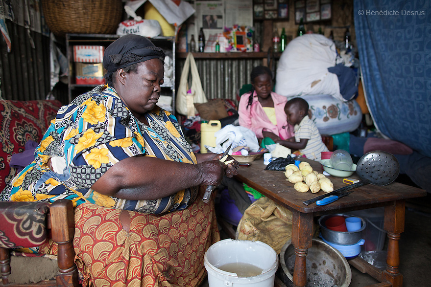 """""""Mama Safi""""peels potatoes at her home inKawangware slum in Nairobi, Kenya on March 25, 2013. Susan Kalai aka """"Mama Safi"""" is a 53 year old Kenyan woman with severe morbid obesity living inKawangware slum in Nairobi, Kenya. Shelives on less than $1 USD a day, selling vegetables and fried potatoes in the street in front of her house. She has 7 children, the youngest one is 9 yearsold. She suffersfrom several obesity-related diseases. She can't walk, has a lot of pain in her legs and back and also has difficulties to breathe. She says """"I was born big. I was always like this.Both my parents and my sister are big too. So for me it's normal. Nothing is wrong with me"""".She has no knowledgeabout obesity and she can't go to the doctor to get treated because she has no money to pay for it. She is afraid to die of a heart attack. Although large parts of Africa areplaguedwith malnutrition, the continent must now also deal with another problem:obesity.Obesity is fast becoming a serious problem in Kenya and even the poorest are now being affected. Obesity rates are climbing around the world and they are rising faster in developing countries than in developed ones. (Photo by Benedicte Desrus)"""