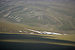 In this aerial view caribou are dotted on the distant residual snow patches.