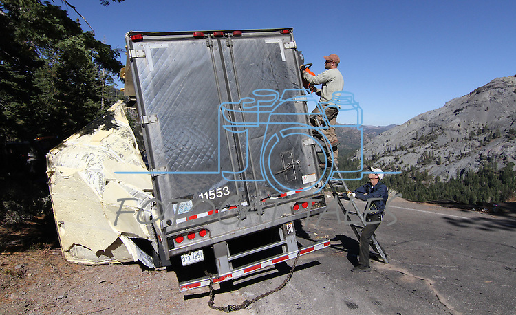 Crews work Tuesday to remove a truck and trailer that crashed over the embankment of Cadillac Curve on Highway 4, south of Markleeville, Ca. on Tuesday, Oct. 12, 2010. The driver survived the August 2010 accident which left peanut butter chips scattered around the wreckage..Photo by Cathleen Allison