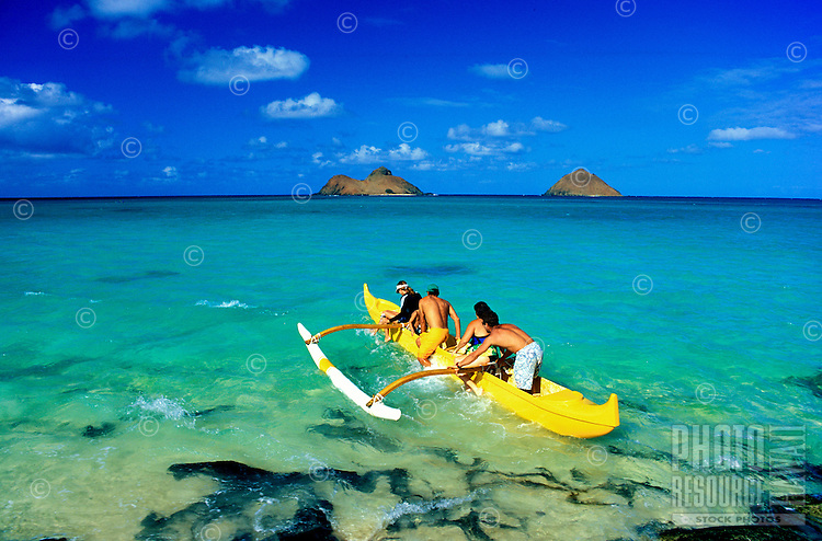 An Outrigger Canoe prepares to head out into the turquois blue waters off Lanikai Beach.  Scenic Moku lua islands in the background.  Windward Oahu.