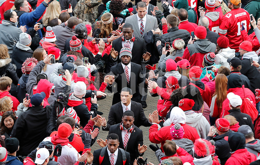 Ohio State Buckeyes quarterback J.T. Barrett (16), center in hat, high fives fans as he makes his way into the stadium before the college football game between the Ohio State Buckeyes and the Michigan Wolverines at Ohio Stadium in Columbus, Saturday morning, November 29, 2014.  (The Columbus Dispatch / Eamon Queeney)