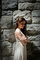 Young woman standing next to stone wall