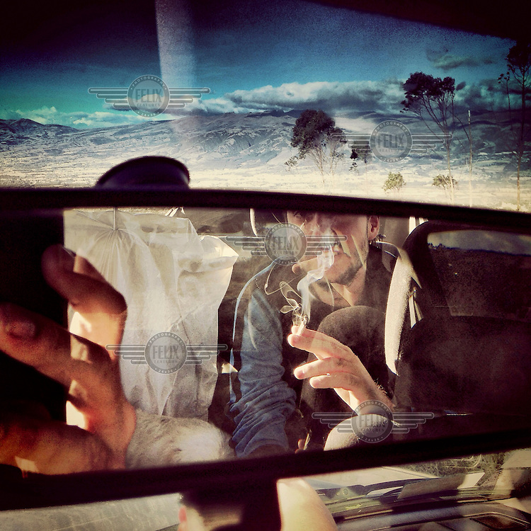 A man smokes in the back of a car on top of Ilalo, an extinct volcano.