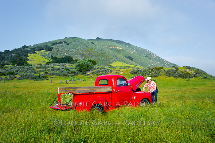 Cowboy checking the engine on  his 1949 Red Ford Truck, San Luis Obispo, California