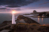 Daybreak at the remote coastal town of Castlepoint on New Zealand's North Island. The lighthouse which sits on top of a cliff 50m above sea level, was first lit in 1913, and today is one of only two lighthouses still fitted with the original lens. Castle Rock can be seem towering above the lagoon in the background.