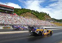 Jun 19, 2016; Bristol, TN, USA; NHRA funny car driver Ron Capps (near) races alongside teammate Jack Beckman during the Thunder Valley Nationals at Bristol Dragway. Mandatory Credit: Mark J. Rebilas-USA TODAY Sports