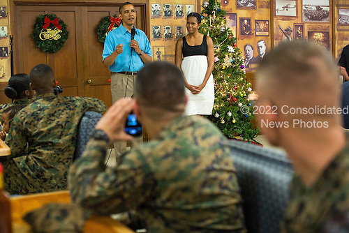 United States President Barack Obama makes remarks as first lady Michelle Obama listens as they greet military personnel eating Christmas dinner at Anderson Hall at Marine Corps Base Hawaii on December 25, 2012 in Kaneohe Bay, Hawaii.  .Credit: Kent Nishimura / Pool via CNP