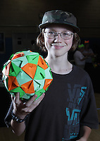 New York, NY, USA - June 24, 2011: Byriah Loper, Origami designer and folder at the OrigamiUSA Convention in New York City, holding his modular polyhedral creation.