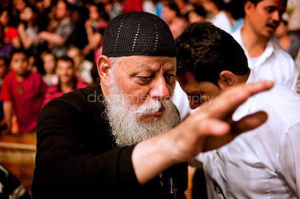 Father Samaan holding his hand to a devoted before performing exorcism.<br />