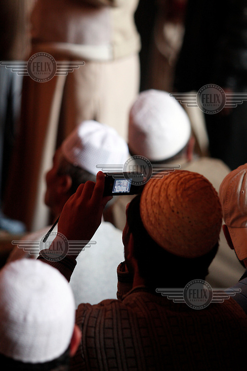 A man photographs with his mobile phone. Friday prayer at the Jamia Masjid mosque led by seperatist leader Umar Mirwaiz. Heading the Hyrriyat Conference, a coalition of seperatist parties, the cleric and politician is considered to be a moderate.  Srinagar, Kashmir, India. © Fredrik Naumann/Felix Features