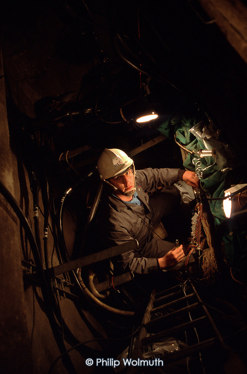 A telephone engineer carries out a night-time repair in North London