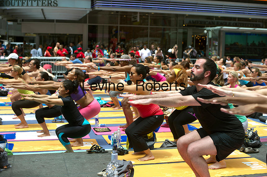 Thousands of yoga practitioners in Times Square in New York participate in a group Bikram Yoga class observing the Summer Solstice at 1:16 PM on Tuesday, June 21, 2011. The classes given throughout the day attract thousands of students of various levels who practiced their art and attempted to find tranquility and transcendence amidst the cacophony and chaos in Times Square on a busy Tuesday afternoon. (© Frances M. Roberts)