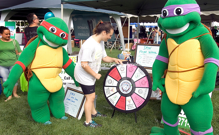 CHESHIRE CT. 06 September 2014-090614SV03-Alexis Shanok, 14, of Cheshire spins the wheel with Ninja Turtles, Sophia Offerdahl, left, and Michael Shidler, right, at the JC Karate booth during The Cheshire Fall Festival and Market Place at Bartlem Park in Cheshire Saturday.<br /> Steven Valenti Republican-American