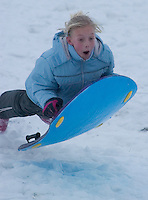 A young girl goes airborne at the bottom of a snow-covered slope on the facing edge of a reservoir dam in Columbus, Ohio, Thursday, December 23, 2004. A winter storm covered central Ohio with as much as a foot of snow and an inch of ice forcing school and business closings.
