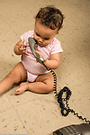 Infant development 9 month old baby girl playing with telephone turning receiver over